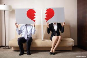 Pärchen sitz auf einer Couch. Die Frau und der Mann halten je ein Schild mit einem gebrochenem Herzen darauf hoch.