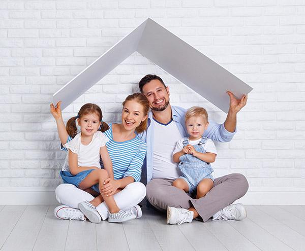 Vater, Mutter und zwei Kinder sitzen unter einem Dach.